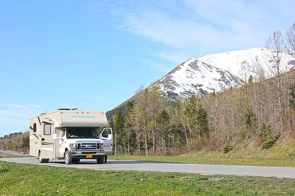 An RV stopped next to a mountain on an Alaskan highway