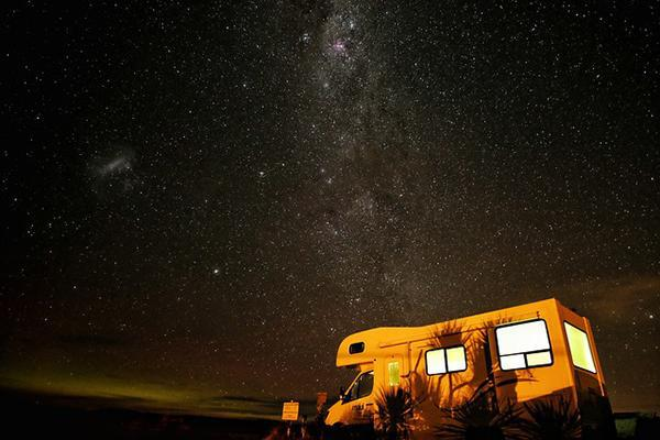 A campervan lit up at nighttime with amazing stars in the sky