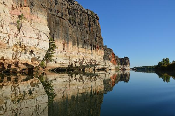 A cliff reflects into the waters of the Kimberley Region in Western Australia