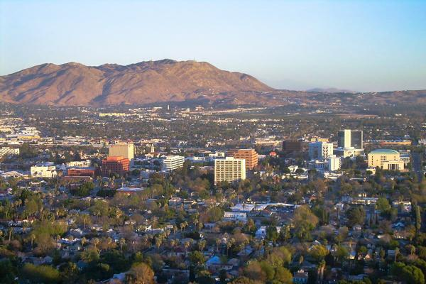 The town of Riverside, California covered in green trees with the desert mountains in the background