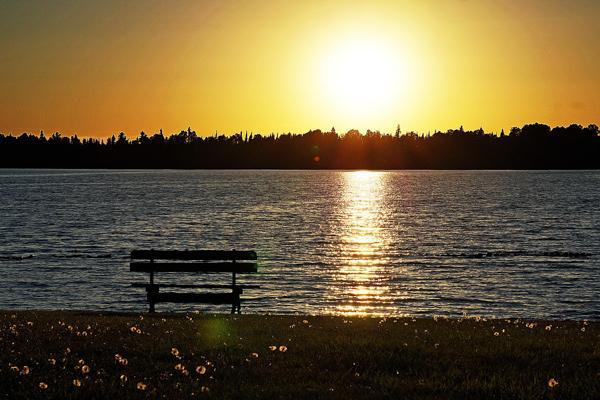 The sun sets over the lake and an empty bench in Ojibway Park near Sioux Lookout, Canada