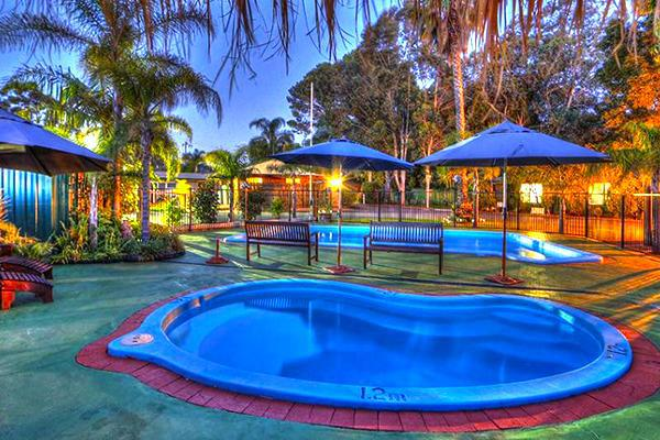 Two inviting pools in an inviting tropical setting at Mandurah Caravan and Tourist Park