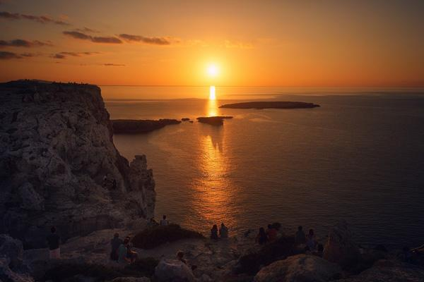 People gather cliffside to watch the setting sun in Menorca, Spain