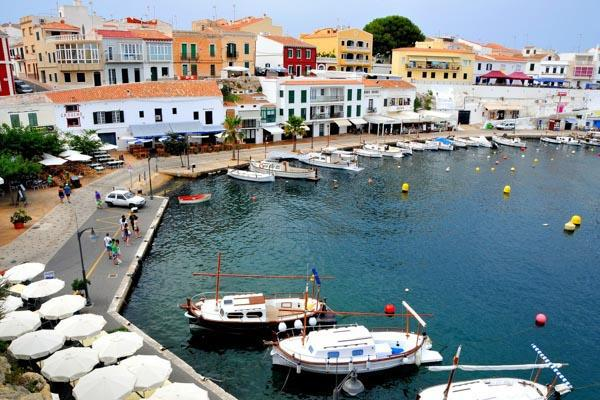 The quaint harbour of Menorca, Spain filled with boats and colourful buildings