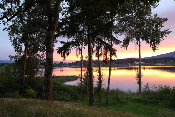 The sun sets over the lake and trees near Port Hardy on Vancouver Island, Canada