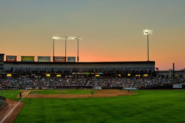 The stadium lights turn on as the sun sets during a baseball game at Round Rock, Texas